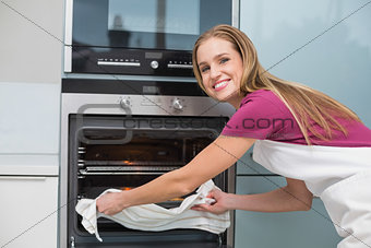 Casual smiling woman putting baking tray in oven