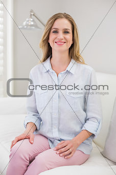 Casual smiling blonde sitting on couch looking at camera
