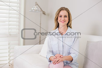 Casual happy blonde sitting on couch looking at camera