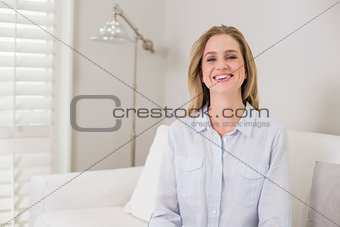 Casual laughing blonde sitting on couch looking at camera