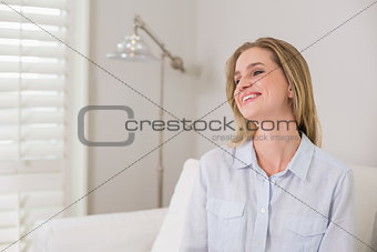 Casual laughing blonde sitting on couch looking away
