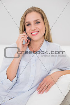 Smiling casual blonde relaxing on couch phoning