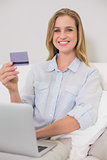 Cheerful casual blonde relaxing on couch doing online shopping