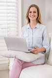 Cheerful casual blonde sitting on couch using laptop