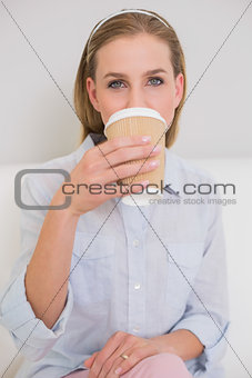 Calm casual blonde sitting on couch drinking from disposable cup