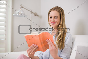Smiling casual blonde sitting on couch reading