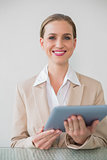 Cheerful stylish businesswoman using tablet