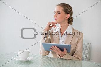 Thoughtful stylish businesswoman using tablet