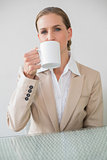 Frowning stylish businesswoman holding mug