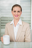 Smiling stylish businesswoman holding mug