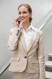 Happy stylish businesswoman phoning