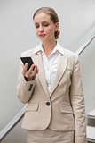 Unsmiling stylish businesswoman holding smartphone