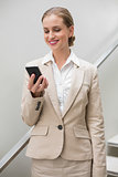 Smiling stylish businesswoman holding smartphone