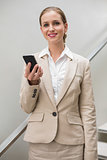 Cheerful stylish businesswoman holding smartphone