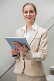 Happy stylish businesswoman holding tablet
