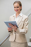 Smiling stylish businesswoman holding tablet
