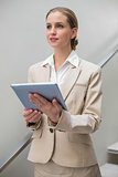 Pensive stylish businesswoman holding tablet