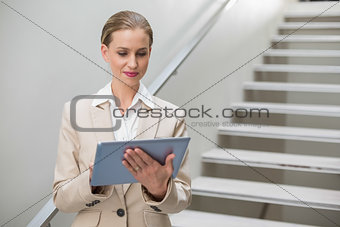 Thoughtful stylish businesswoman looking at tablet