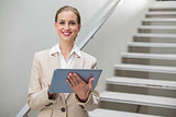 Cheerful stylish businesswoman holding tablet