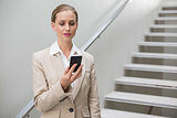 Thoughtful stylish businesswoman holding smartphone