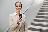 Laughing stylish businesswoman holding smartphone