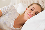 Natural calm woman sleeping in bed