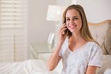 Natural cheerful woman sitting in bed phoning