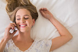 Natural smiling woman lying on bed phoning