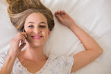 Natural cheerful woman lying on bed phoning