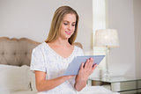 Natural happy woman sitting on bed holding tablet