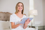 Natural laughing woman sitting on bed holding tablet