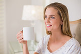 Natural happy woman sitting on bed holding mug