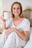 Natural smiling woman sitting on bed holding mug