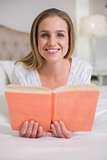 Natural cheerful woman lying on bed holding book