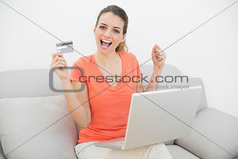 Beautiful cheering woman presenting her credit card sitting on couch