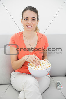 Attractive smiling woman eating popcorn while watching television
