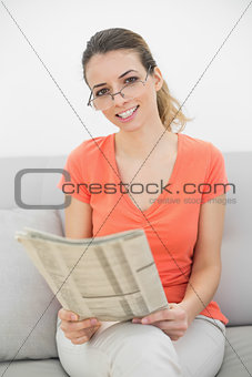 Beautiful ponytailed woman holding a magazine sitting on couch
