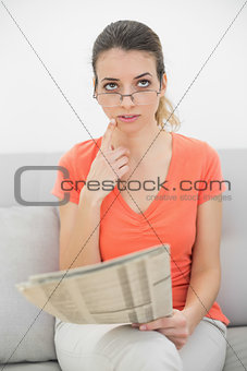 Thoughtful young woman sitting on couch holding a magazine