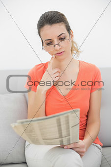 Attractive woman reading a magazine sitting on couch