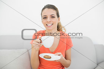 Attractive brunette woman holding a cup smiling cheerfully at camera