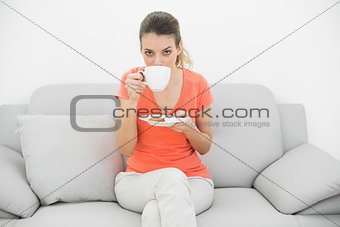 Pretty young woman drinking of cup looking at camera