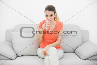 Attractive casual woman drinking a glass of water looking at camera