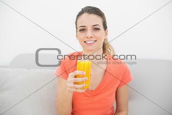 Beautiful calm woman smiling at camera holding a glass of orange juice