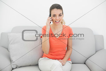 Amused ponytailed woman phoning looking at camera