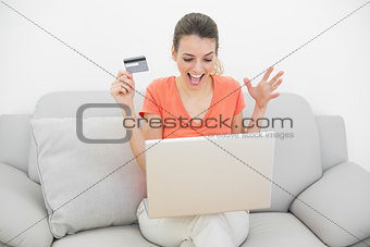 Beautiful happy woman home shopping with her notebook sitting on couch