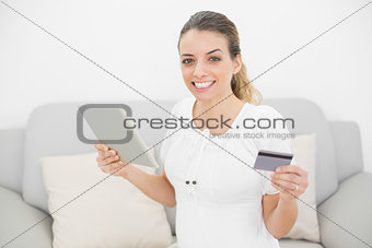 Attractive pregnant woman showing cheerfully her credit card and tablet