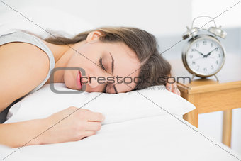 Attractive calm woman lying on her bed under the cover sleeping