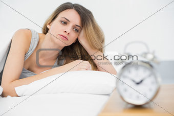 Tired young woman lying under the cover on her bed