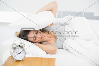 Cute tired woman covering her ears with pillows