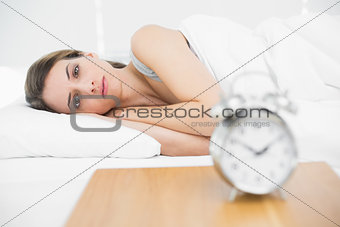 Calm attractive woman lying on her bed